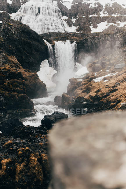 Cascada que fluye de oscuras rocas negras - foto de stock