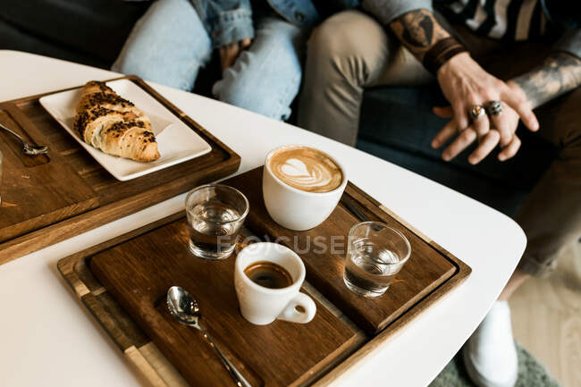 Crop unrecognizable people sitting in cafe at table with cups of coffee. — Stock Photo