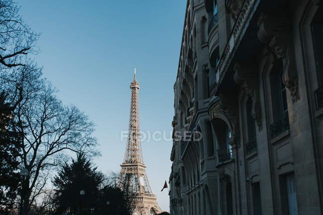 Ейфелева вежа в безхмарне день та історичній будівлі на вулиці в Парижі — стокове фото