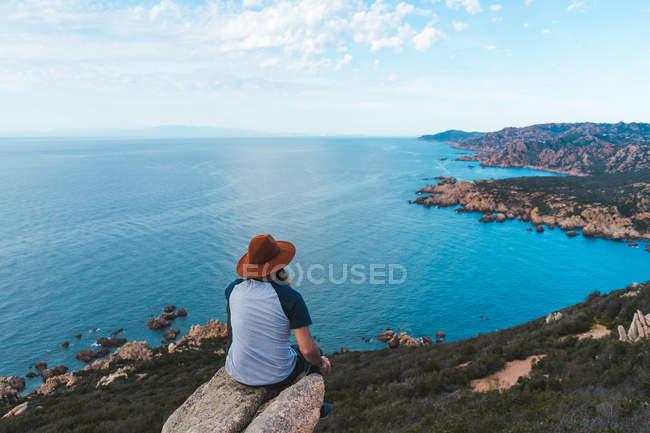 Homem de chapéu sentado na rocha à beira-mar — Fotografia de Stock