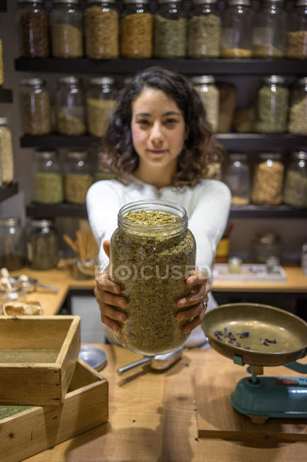Woman showing jar of spices — Stock Photo