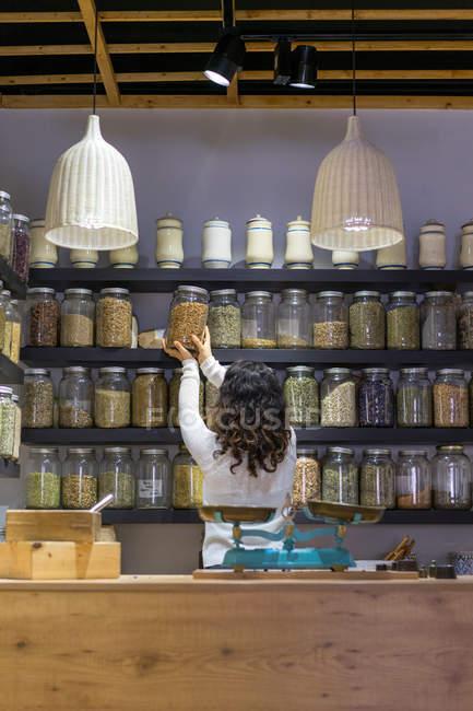 Жінка бере банку з спецій у магазин — стокове фото