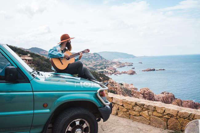 Homem tocando guitarra no telhado do carro — Fotografia de Stock