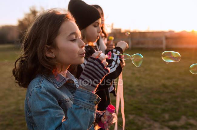 Діти бавляться з мильними бульбашками. — стокове фото