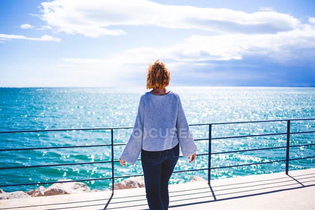 Femme debout à la main courante et regardant l'océan — Photo de stock