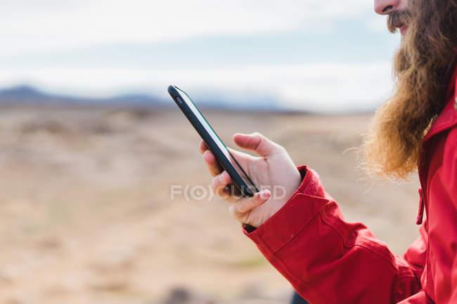 Homme debout avec smartphone chez geyser — Photo de stock