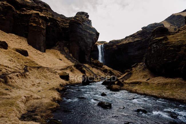 Waterfall in rocky cliffs — Stock Photo