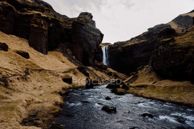 Waterfall in rocky cliffs — Stock Photo