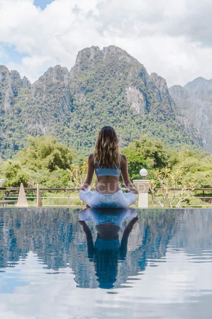 Жінка медитації біля басейну — стокове фото