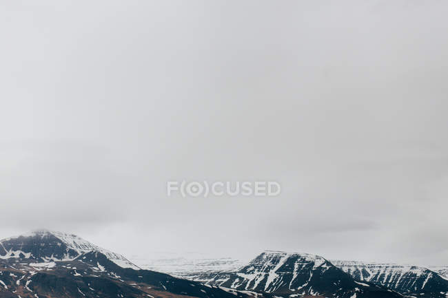 Mist covering rocky range of mountains — Stock Photo