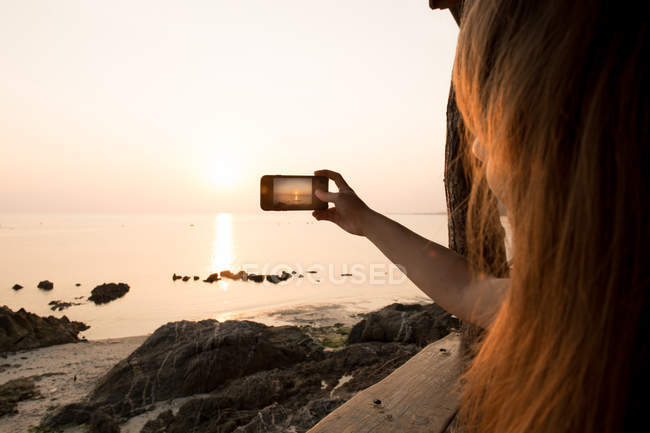 Donna che cattura foto in riva al mare — Foto stock