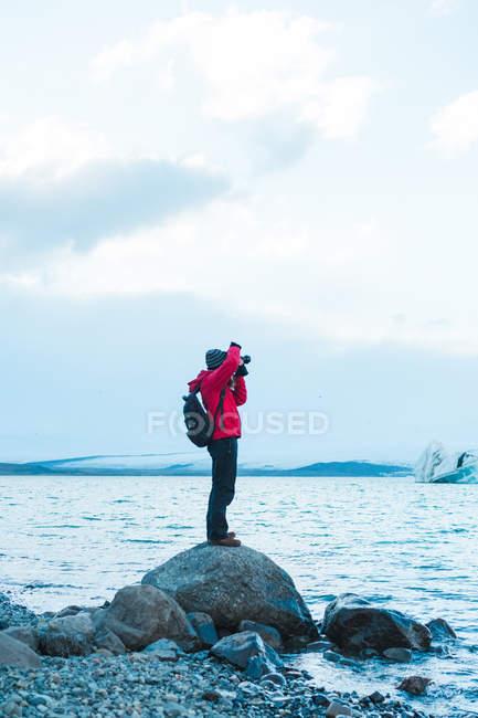 Homme en vêtements chauds prenant des photos du lac — Photo de stock