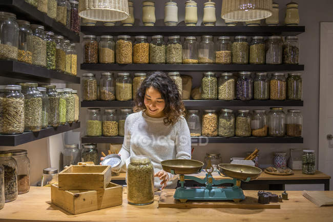 Woman opening jar with spices — Stock Photo