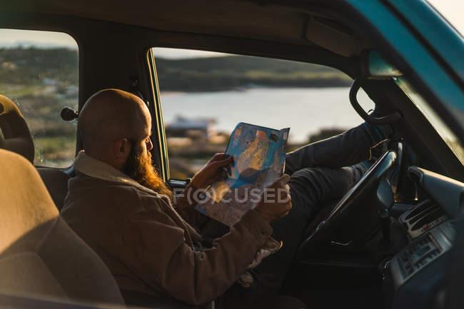 Homme assis dans la voiture et la tenue de carte — Photo de stock