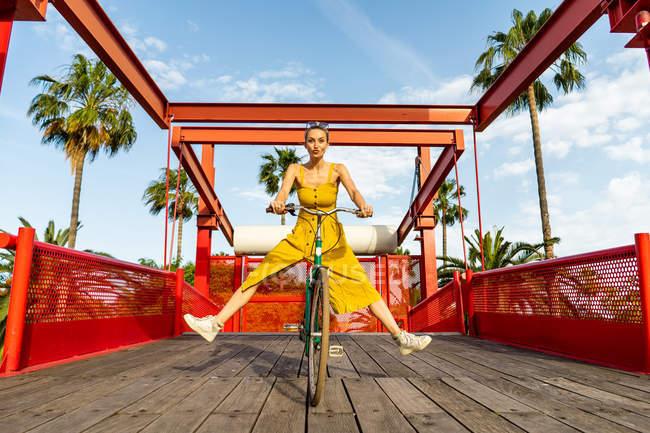 Mulher de vestido amarelo andar de bicicleta — Fotografia de Stock