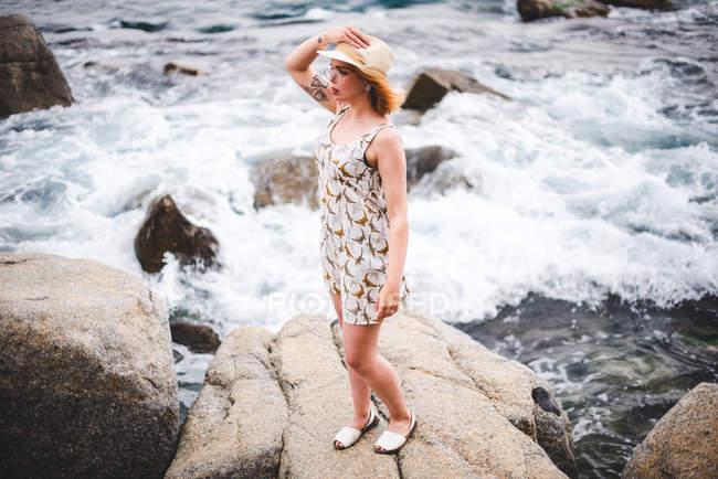 Женщина в шляпе, стоящая на камнях — стоковое фото