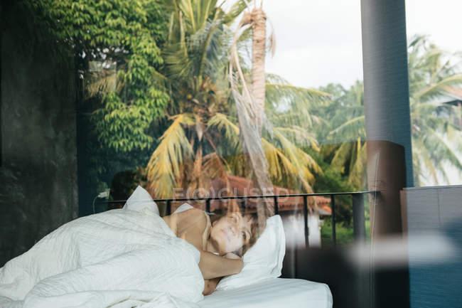 Woman lying in bed in tropics — стокове фото
