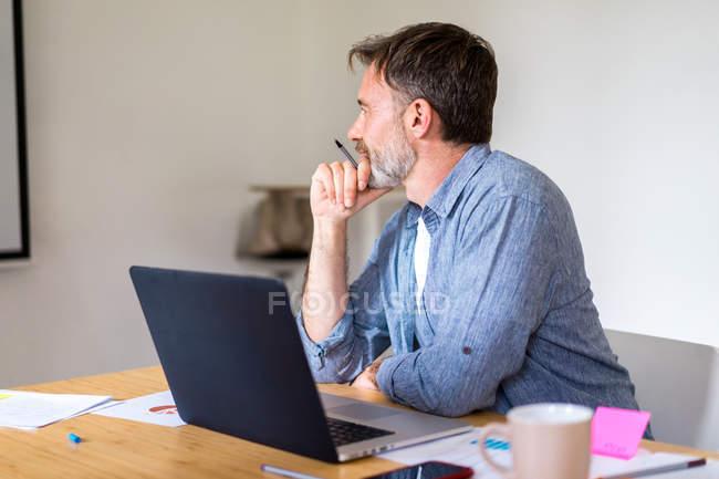 Людина, сидячи за столом з ноутбуком — стокове фото
