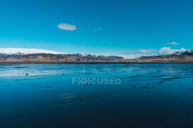 Відливу на узбережжі і снігові гори — стокове фото