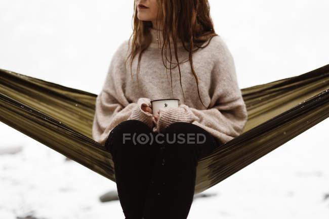 Жінка сидить в гамаку, підвішеному в зимовий період — стокове фото
