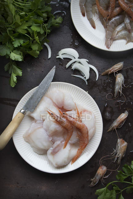 Raw shrimps and fish fillet served on a plate on black surface — Stock Photo