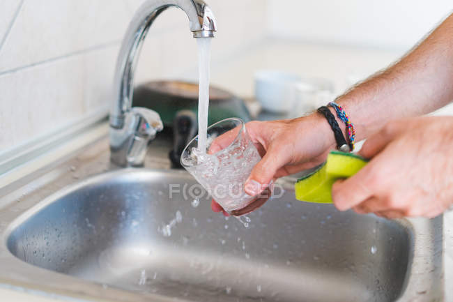 Hands washing glass in sink — Stock Photo