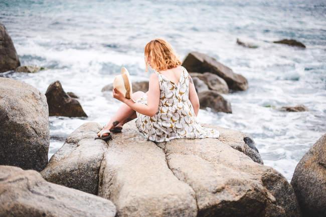 Femme rousse assise sur rocher à ocean — Photo de stock