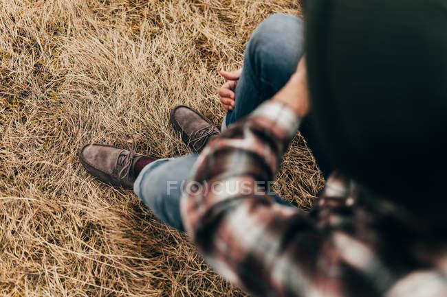 Человек, сидящий на соломенной траве — стоковое фото