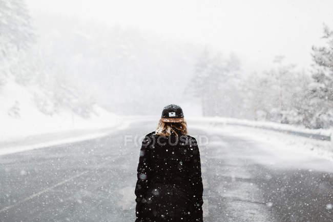 Жінка ходьба по сніговій дорозі — стокове фото