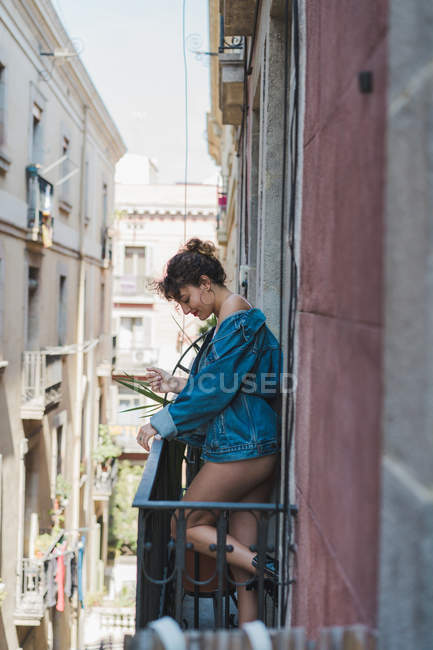 Woman in denim jacket standing on balcony — Stock Photo
