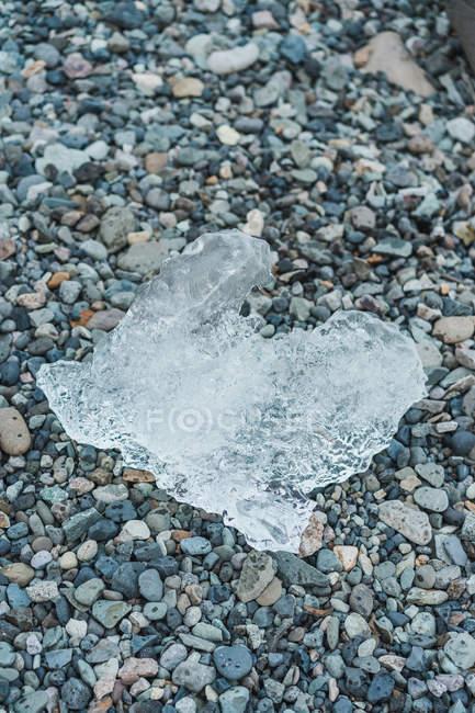 Кусок льда на камнях — стоковое фото