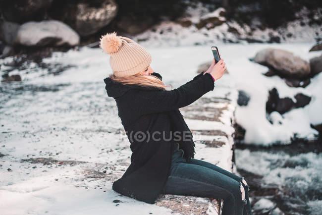 Donna che prende selfie al fiume in inverno — Foto stock