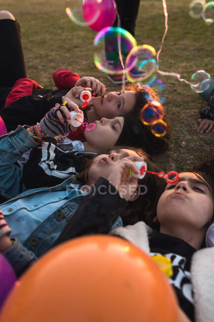Gruppo di bambini alla moda che si divertono e soffiano bolle di sapone mentre sono sdraiati a terra nel parco. — Foto stock