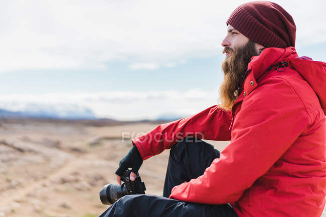 Man with camera sitting in barren land — Stock Photo
