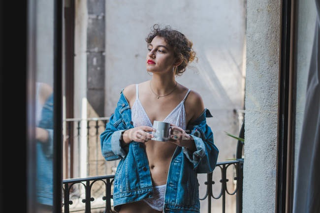 Woman in denim jacket holding cup on balcony — Stock Photo