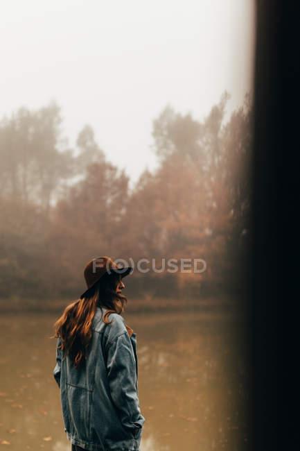 Frau mit Hut steht am Teich — Stockfoto