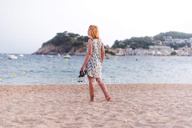 Donna che trasporta Sandali sulla spiaggia — Foto stock