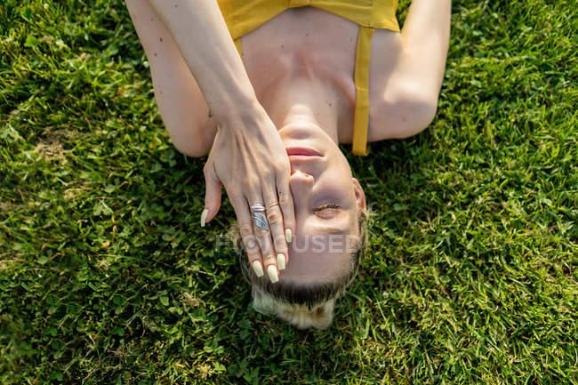 Mulher deitada na grama e cobrindo de rosto — Fotografia de Stock