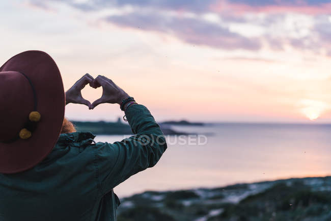 Man gesturing heart on coast — Stock Photo
