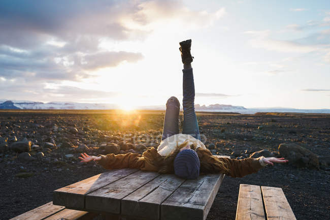 Женщина лежит на деревянном столе на закате — стоковое фото