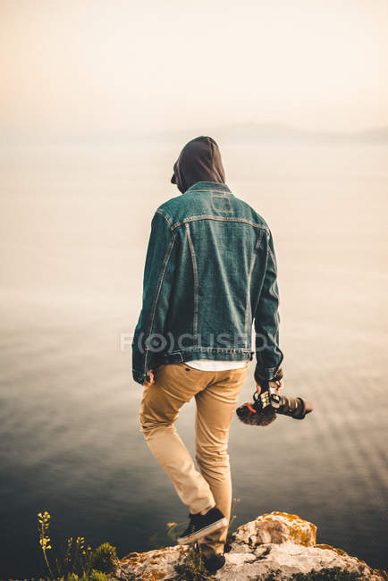 Man with camera walking on promontory — Stock Photo