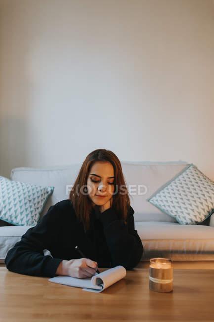 Женщина пишет в блокноте — стоковое фото