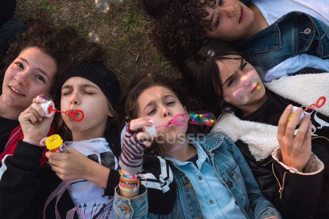 Kids playing with soap bubbles on lawn — Stock Photo