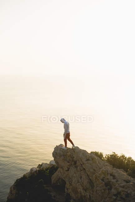 Homme debout sur une falaise rocheuse — Photo de stock