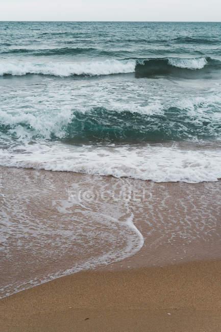 Océano azul ondulado y surf - foto de stock