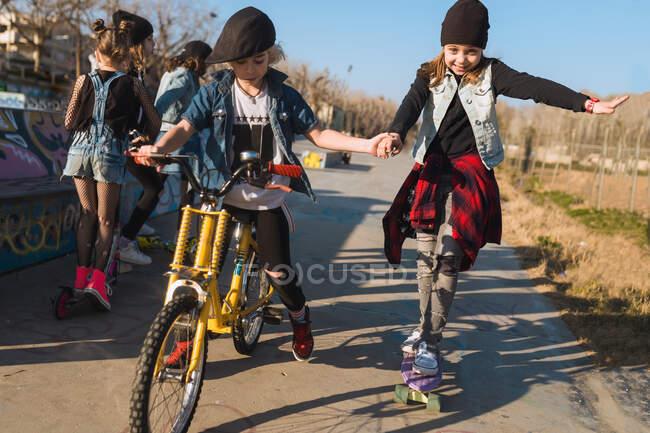 Мальчик ездит на велосипеде и помогает стильной девушке со скейтбордингом весело провести время в скейт-парке. — стоковое фото