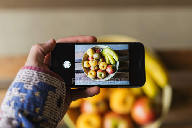 Human hand taking photo of fresh fruits in bowl with smartphone — Stock Photo