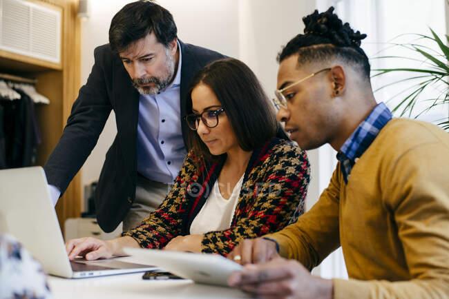 Pessoas que trabalham no laptop no escritório — Fotografia de Stock