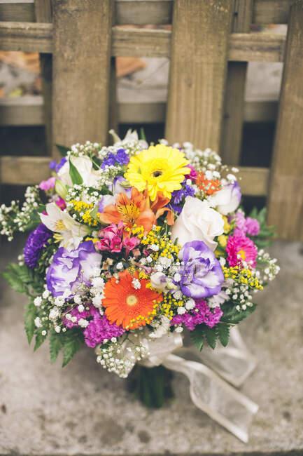 Букет разноцветных цветов на столе и спортивный велосипед в помещении. — стоковое фото