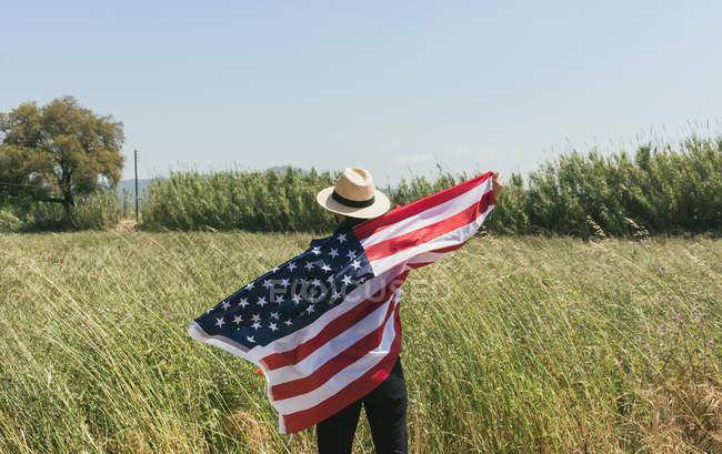 Homem de pé com bandeira americana — Fotografia de Stock